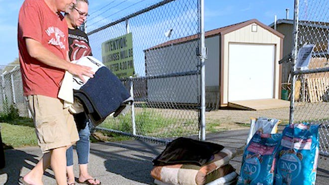 Jim Riegsecker and Jennifer Weinberg, both of White Pigeon, donated items Thursday at St. Joseph County Animal Control in Centreville. The agency is facing an unprecedented situation after taking in more than 200 cats between two hoarding incidents in the past week.