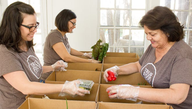 Sisters Vanessa Brady, left, and Adriana Clowe (back) and mother Patsy Terrazas-Hermosillo sort fresh produce as part of their business, True Foods.
