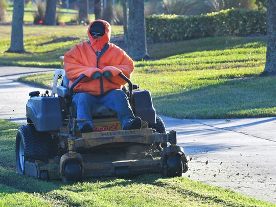 Crew members of Tropic-Care of Florida were on the job at dawn in the cold weather in the low 30s on Thursday morning in Viera.