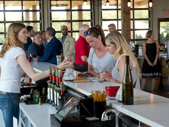 Visitors to Sharrott Winery sample wine at one of the new tasting room bars.