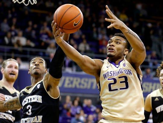 Washington guard Carlos Johnson grabs a rebound in front of Western Michigan guard Josh Davis in the first half of an NCAA basketball game, Sunday, Dec. 18, 2016, in Seattle. (AP Photo/Ted S. Warren)