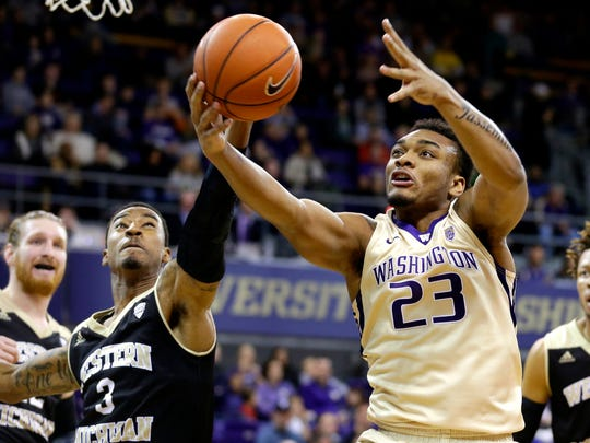 Washington guard Carlos Johnson grabs a rebound in front of Western Michigan guard Josh Davis in the first half of an NCAA basketball game, Sunday, Dec. 18, 2016, in Seattle. (AP Photo/Ted S. Warren)