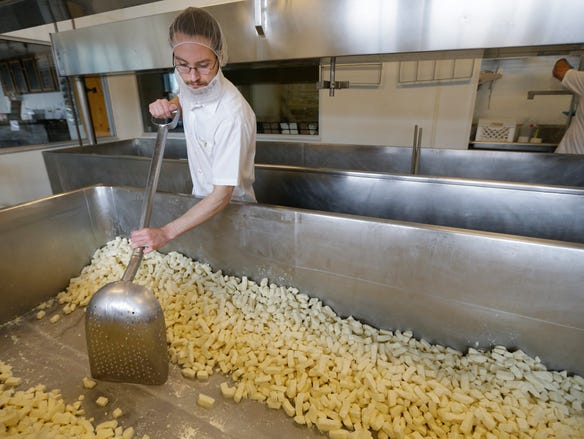 Mike McMahon, an assistant cheese maker, works on scooping