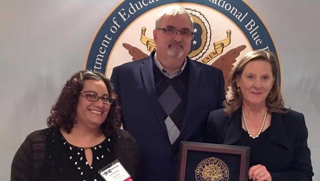 were (left to right), Arrowhead Park Early College High School English teacher Lynette Defreitas, left, Superintendent Greg Ewing and APECHS Principal Jennifer Amis receive the school's Blue Ribbon Award in Washington, D.C. on Tuesday, Nov. 7, 2017.