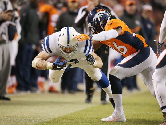 Indianapolis Colts tight end Jack Doyle dives for extra yards past Denver Broncos free safety Rahim Moore in the second half. Indianapolis faced Denver in the NFL playoffs Sunday, January 11, 2015.