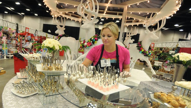 Junior League of Jackson member helps arrange a display of sweet treats at the Mississippi Trade Mart.