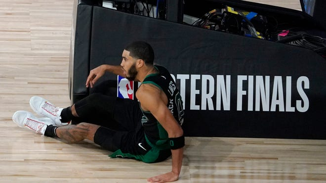 Boston Celtics' Jayson Tatum (0) sits on the floor after his shot attempt was blocked by Miami Heat's Bam Adebayo, not pictured, in the closing seconds of overtime of an NBA conference final playoff basketball game, Tuesday, Sept. 15, 2020, in Lake Buena Vista, Fla.