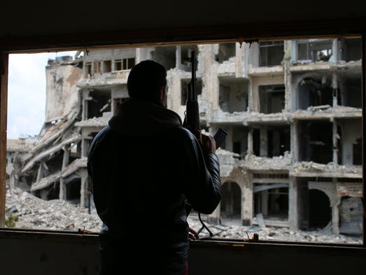 A Syrian rebel fighter stands behind a window in a