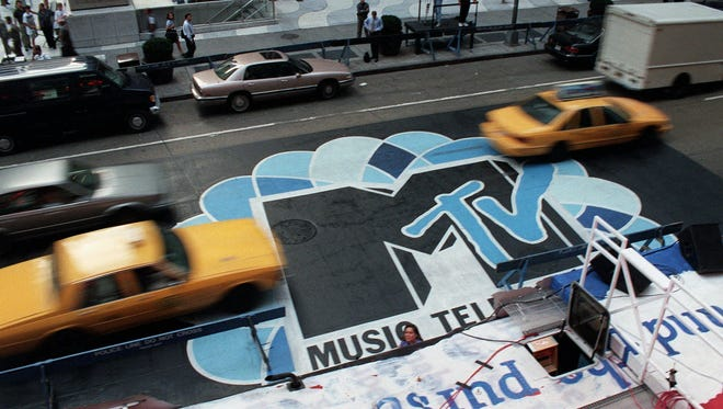 Traffic moves along 6th Avenue in New York, over the logo painted in the street outside Radio City Music Hall in 1996.
