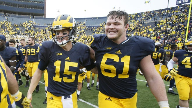 Michigan quarterback Jake Rudock (15) and offensive lineman Graham Glasgow (61) walk off the field following a 35-7 win against Oregon State at Michigan Stadium in Ann Arbor, Mich., on Saturday, Sept. 12, 2015.