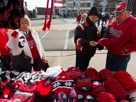 Fans browse merchandise being sold by Robb Polinske  before the Wisconsin-Minnesota football game Saturday outside Camp Randall Stadium in Madison.