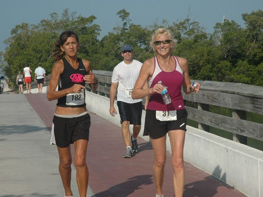 Loretta Purish of North Fort Myers and Astrid Soll of Fort Myers run over the bridge at Lovers Key State Park during the Turtle Trot event.