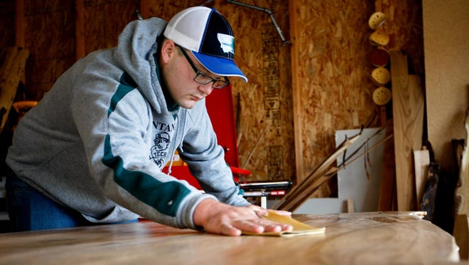 Andrew Bishop of River Bottom Restoration Furniture does a final sanding on a large table he is working on in his garage west of Billings on Oct. 9.