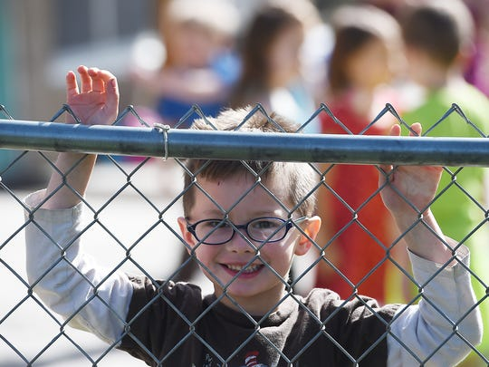 Zayden Slone, 5, looks through the fence at his mother