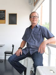 Billy Seckman, owner of the coffeehouse Bean, sits