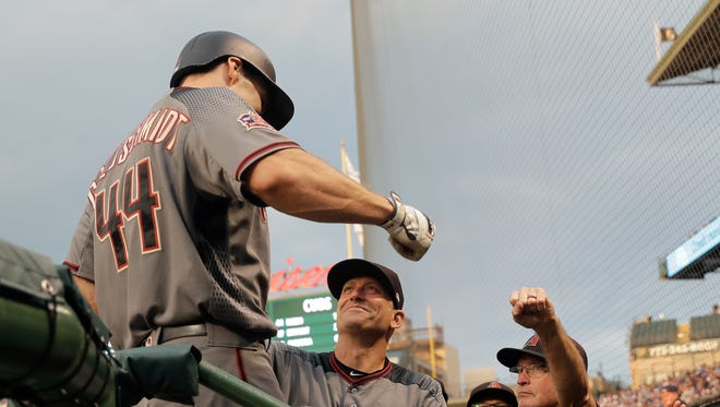 Arizona Diamondbacks' Paul Goldschmidt (44) is greeted in the dugout by manager Torey Lovullo, center and bench coach Jerry Narron, after Goldschmidt 's home run off Chicago Cubs starting pitcher Luke Farrell during the second inning of a baseball game Monday, July 23, 2018, in Chicago.