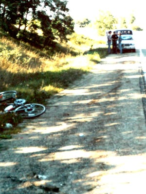 Shawn Moore's bicycle is seen lying alongside Whitmore Lake Road in Green Oak Township while a police officer talks with two people in the background. Witnesses said they saw a white male force 13-year-old Shawn into a Jeep on Aug. 31, 1985.