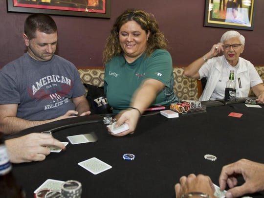 """Heather """"Lefty"""" Schneck, 36, manages a poker game at Nemo's at HeadPinz in Cape Coral Tuesday (09/0115). Schneck lost her arm in a car crash in 2008. The driver was drinking. She's an avid poker player and is now a dealer and deals throughout Cape Coral."""