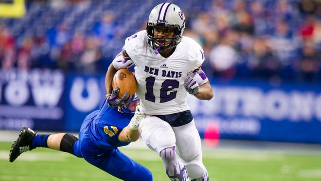 Ben Davis High junior Chris Evans (12) eludes the tackle of Carmel High sophomore Daniel Popowics during the IHSAA Class 6A state championship game Nov. 28, 2014, in Indianapolis.