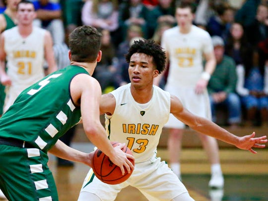York Catholic's D'Andre Davis, right, defends against Trinity's Mike Scarpelli during boys' basketball action at York Catholic High School in York City, Saturday, Dec. 9, 2017. Trinity would win the game 56-42. Dawn J. Sagert photo