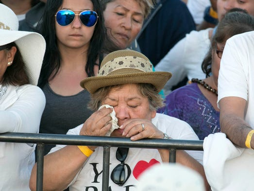 A woman cries during mass at the fairgrounds in Ciudad