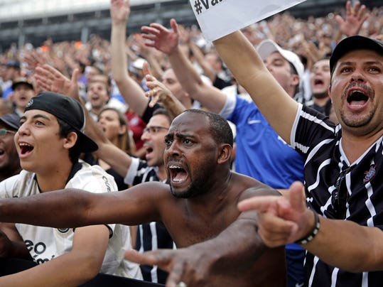 Corinthians's supporters cheer during a Brazilian soccer league match at the Itaquerao, the still unfinished stadium, in Sao Paulo, Brazil, Sunday, May 18, 2014. Only 40,000 tickets were put on sale for Corinthians' match against Figueirense because some of the 20,000 temporary seats needed for the World Cup opener are still being installed. The stadium will host the World Cup opener match between Brazil and Croatia on June 12. (AP Photo/Andre Penner)