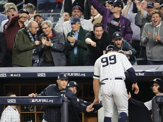 Yankee fans cheer for Aaron Judge (99) as he is congratulated by Yankees Manager, Joe Girardi.  Judge scored on a single by Gregorius (not shown) in Game 5, Wednesday, October 18, 2017.