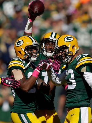 Green Bay Packers strong safety Micah Hyde (33), right, celebrates his interception with cornerback Casey Hayward (29) and cornerback Sam Shields (37) against St. Louis Rams at Lambeau Field.