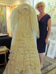 Betty Newman next to her mother's antique wedding gown.