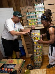 Lance Guy, left, and Christopher Yates, unloads a shipment