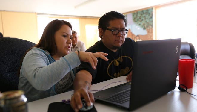 Marty Buck, left, works with Krieg Benally on her project Wednesday during a coding class at All Saints Church in Farmington.