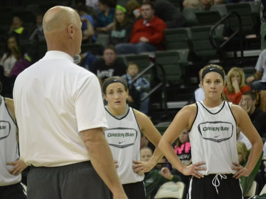 UWGB freshman guards Jen Wellnitz, center, and Laken James, right, listen as coach Kevin Borseth addresses the crowd at the end of a preseason scrimmage last Saturday at the Kress Events Center.