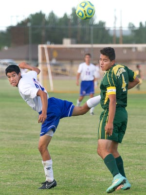 Las Cruces High's Dylan Udero tries to find the ball after he and Mayfield's Chico Franco battled for the goalie's kick Thursday night at the Field of Dreams Soccer Complex.