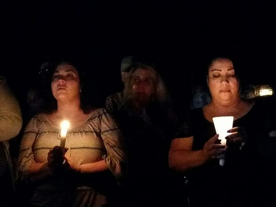 Kassandra Holguin, left, Naomi Meyers and Diana Rodriguez participate in a vigil for slain Hatch Officer Jose Chavez on Saturday night in front of the Hatch Valley Regional Public Safety Building.