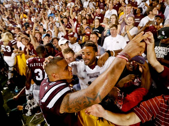 Mississippi State quarterback Dak Prescott (15) celebrates with fans at Tiger Stadium after the Bulldogs' 34-29 victory over LSU Saturday night.