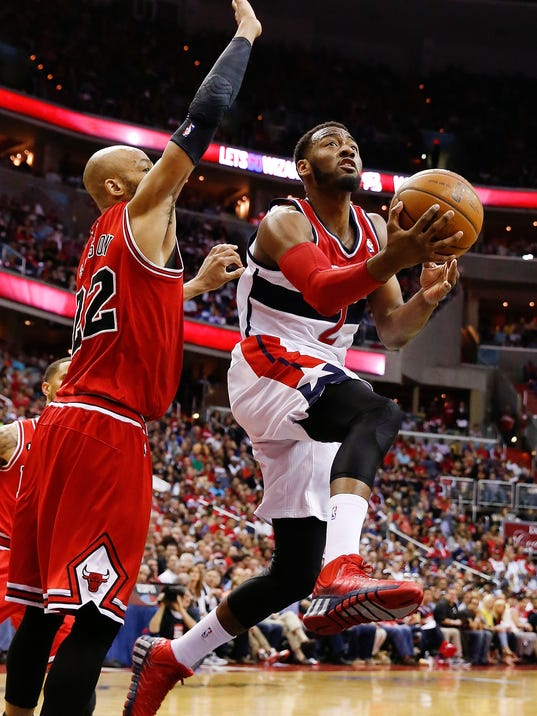 Washington Wizards guard John Wall (2) shoots under pressure from Chicago Bulls forward Taj Gibson (22) during the second half in Game 4 of an opening-round NBA basketball playoff series in Washington, Sunday, April 27, 2014. (AP Photo/Alex Brandon)