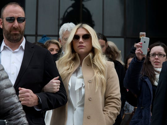Pop star Kesha, center, leaves the Supreme Court in