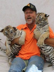 Tim Stark, owner of Wildlife in Need Inc., holds two of his tiger cubs.