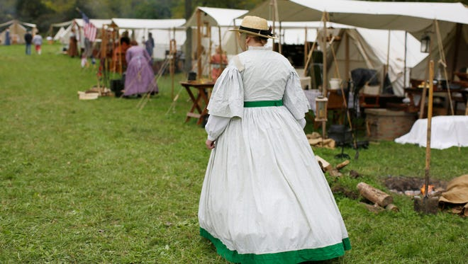 A woman walks in period dress Saturday Sept. 24, 2016, during the Civil War Weekend at the Wade House Historical Site in Greenbush.