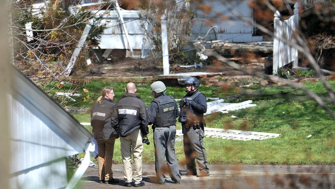 A bomb squad member and Ohio State Highway Patrol troopers stand in front of 36 Randall Road after a standoff in April.