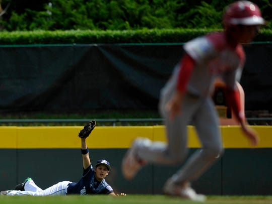 """""""Red Land's Adam Cramer holds up his glove after making"""