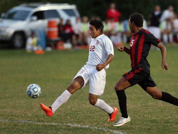 Jeffersonville's Martin Ojeda (#22)  gets past New Albany's Nick Davis and uses a light touch to score the goal just over the keepers reach. Sept. 23, 2014