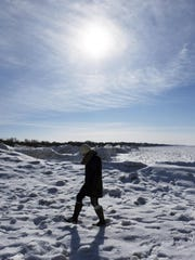 A woman makes her way over the ice-covered south pier,