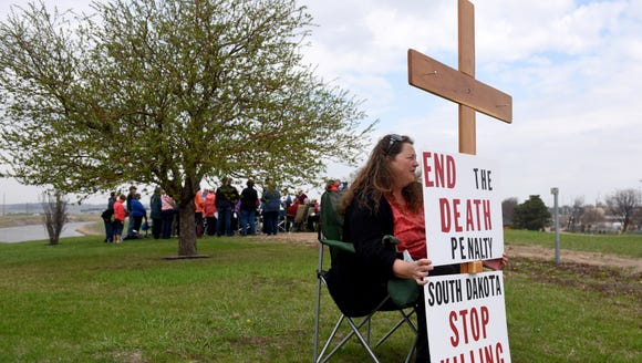 Elaine Engelgau holds a sign and cross during the 20th
