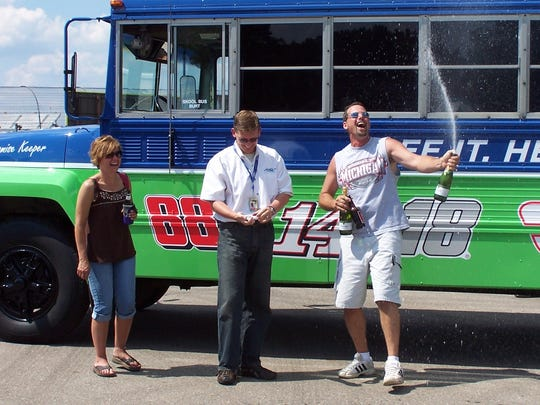 Moe Clark pops his cork after Michigan International Speedway workers unveiled the makeover they did on Clark's old school bus Thursday, Aug, 13, 2009. Clark and his wife, Robyn (left), refurbished the inside of the bus in the fashion of a motorhome a few years ago. MIS workers spruced up the exterior this week. MIS president Roger Curtis is in the middle.