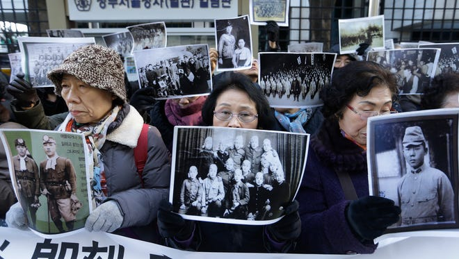 South Korean bereaved family members of victims of World War II stage a rally demanding full compensation and apology from Japanese government in front of Foreign Ministry in Seoul, South Korea, Dec. 28, 2015.