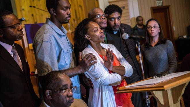 In this Monday, Dec. 1, 2014, photo, Claudia Lacy, center, cries as she thanks the people that showed up at First Baptist Church in Bladenboro, N.C., to listen to the Rev. Dr. William Barber II, president of the North Carolina State Conference of the NAACP, talk about the developments in the investigation of her son's death.