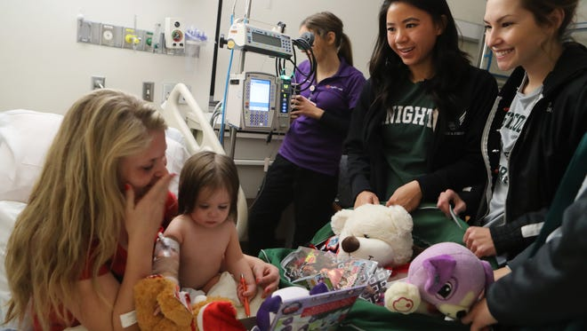 Cassandra Alderman, left, of Redding receives gifts with her 1-year-old daughter Camille Alderman from Shasta College students and track athletes, Jade Permenter, center right, Sabrina Peppel and Christine Rhyne on Wednesday at Mercy Medical Center in Redding. The presents are from a toy drive held at the college in November.