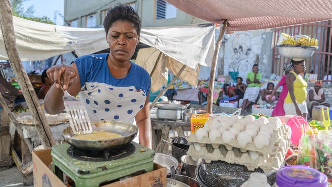Phita, 36, a vendor prepares an omelet sandwich at the Salomon market in Haiti's capital, Port-au-Prince. Most market vendors use eggs brought in illegally from the Dominican Republic because domestic eggs are too expensive. Phita did not give her last name.