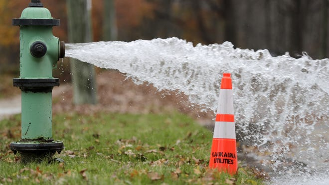 A southside fire hydrant, one of a half dozen city wide, is open in an effort to help flush the city's water system on Tuesday, November 8, 2016, in Kaukauna, Wis.